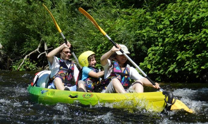 Kayak biplace avec un enfant assis au milieu.